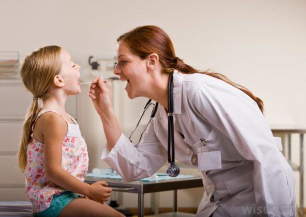 Храпящую девочку осматривает оториноларинголог.