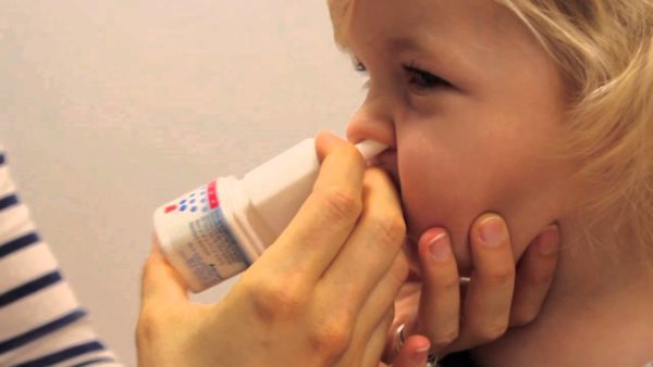 Мама закапывает ребенку нос при насморке.
