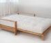 Матрас на деревянной кровати.